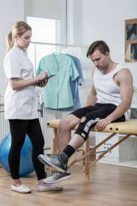 Man after knee ligament injury in physiotherapist's office